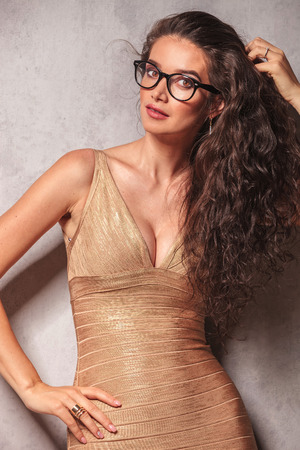 decolletage: beautiful brunette wearing glasses poses while fixing her hair and looking at the camera Stock Photo