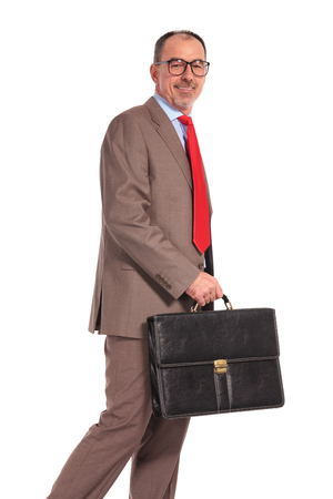 mature business man: side view of a smiling old businessman with briefcase walking on white background