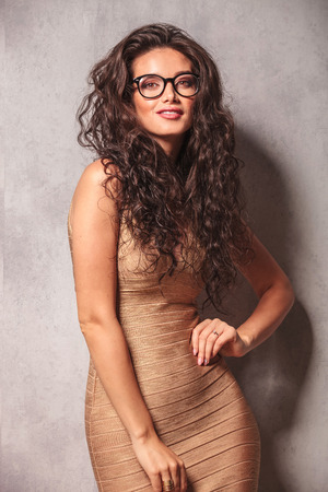 woman hairstyle: attractive woman in sexy dress wearing glasses poses looking at the camera while touching her hip Stock Photo