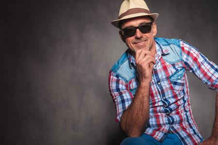 poses de modelos: Hombre mayor sonriente con gafas de sol y sombrero de verano ocasionales que se sientan en una silla en el estudio