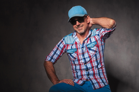 trucker: cool mature casual man in jeans clothes and trucker hat posing with hand behind his neck and smiles