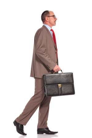 standing businessman: side view of a senior businessman holding suitcase and walking on white background Stock Photo
