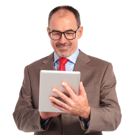 businessman working at his computer: old businessman working on his tablet computer on white background