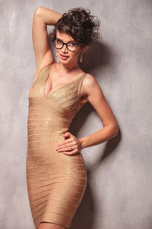 sexy dress: woman in sexy dress wearing glasses pose while fixing her hair and resting her arm on her waist Stock Photo