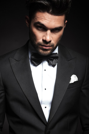 Portrait of a handsome elegant business man looking at the camera with, lifting one eyebrow. Фото со стока