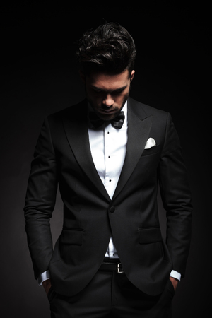 man looking down: Portrait of a elegant young business man looking down while holding both hands in his pocket. Stock Photo