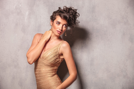 arching: curly woman in sexy dress pose arching her back while touching her neck Stock Photo