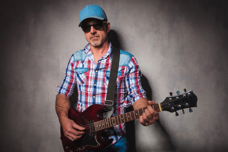 50 years old man: serious old guitarist playing his electric guitar while standing in studio wearing hat and sunglasses Stock Photo