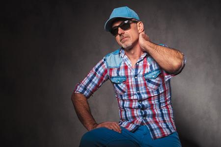 hombre con sombrero: cansado anciano ocasional con el sombrero de béisbol y gafas de sol mira hacia arriba mientras sostiene la parte posterior de su cuello
