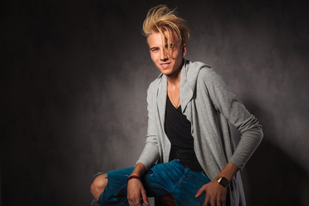 sexy pose: blond fashionable young man wearing rugged jeans posing while sitting in studio background