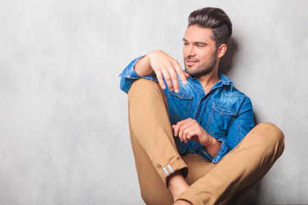 male face: handsome model sitting in studio background legs crossed while looking away