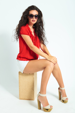 shorts: gorgeous woman looking surprised while sitting on a chair in studio wearing sunglasses Stock Photo