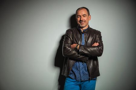 mani incrociate: felice alti uomo casual in giacca di pelle in piedi con le mani incrociate e sorrisi