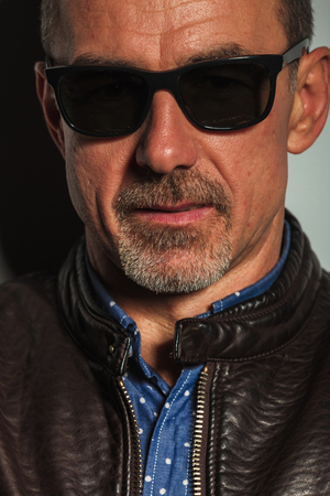 50 years old man: close up portrait of an old casual man in leather jacket and sunglasses , studio picture Stock Photo