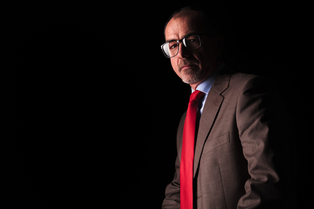 40 year old man: side view of a senior business man wearing glasses on black studio background Stock Photo