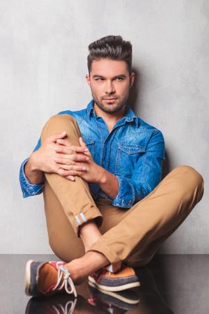 modelos hombres: hombre con estilo que se sienta en las piernas estudio fondo cruzados sosteniendo su rodilla mientras mira lejos Foto de archivo