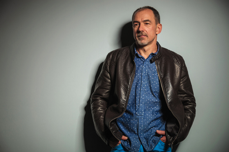 40 year old man: casual senior man in leather jacket looking away to side in studio Stock Photo