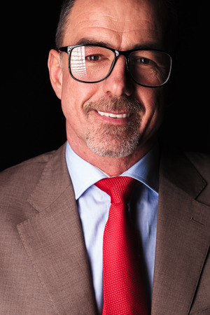 40 years old man: closeup portrait of a mature business man smiling to the camera on black background