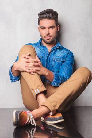 legs crossed at knee: stylish man sitting in studio background legs crossed holding his knee while looking at the camera