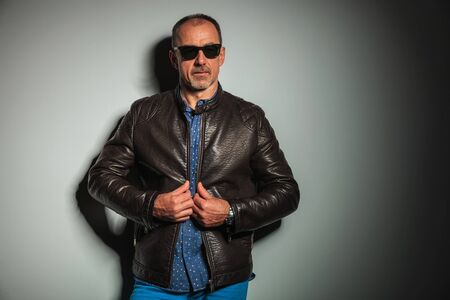 50 years old man: casual old man pulling his leather jacket and looks away from the camera Stock Photo