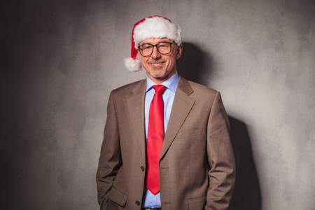 50 years old man: relaxed santa claus business man standing with hands in pockets and smiles in studio Stock Photo
