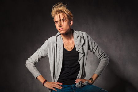 hands on waist: serious blond man posing in studio background while looking away with hands on waist