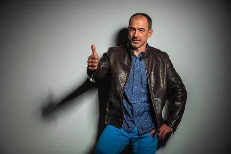 americana: viejo hombre casual en la chaqueta de cuero haciendo los pulgares OK encima de la muestra contra la pared gris del estudio Foto de archivo