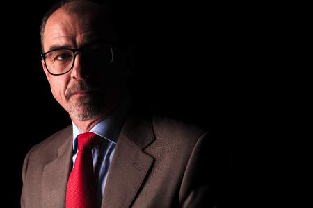 hombre rojo: la cara de un hombre de negocios de alto mirando a lado sobre fondo negro Foto de archivo