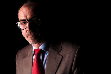 50 years old man: serious mature business man wearing glasses looks to the camera on black studio background