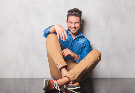 piernas hombre: Hombre sonriente en camisa de mezclilla sentado piernas cruzadas en el estudio de fondo descansando su brazo en su pierna Foto de archivo