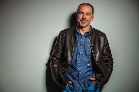 studio portrait: smiling old casual man in leather jacket with hands in pockets standing against gray studio wall Stock Photo