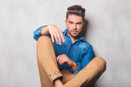 young male: portrait of casual hansome man in denim shirt sitting in studio legs crossed Stock Photo