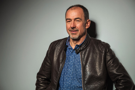 portrait of a relaxed smiling mature casual man in leather jacket looking at the camera