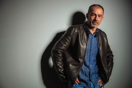 40 year old man: confident old casual man in leather jacket and jeans standing with hands on hips in studio Stock Photo
