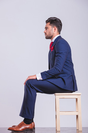 on hands and knees: side portrait on man in suit sitting in studio with hands on his knees
