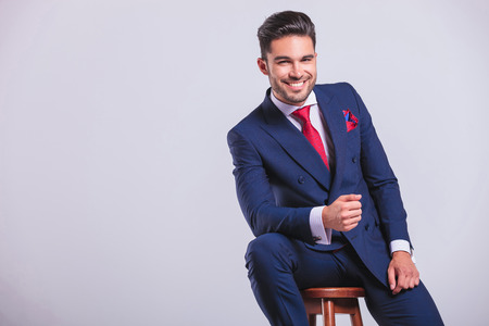 elegant business man leaning while sitting and smiling in studio