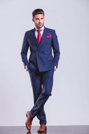 cuerpo hombre: hombre elegante grave posando con las manos en los bolsillos mientras se mira lejos
