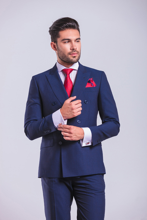 men in suit: side portrait of elegant man in suit looking away while unbuttoning his shirt Stock Photo