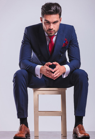 corporate young man sitting in studio with palms touching while posing