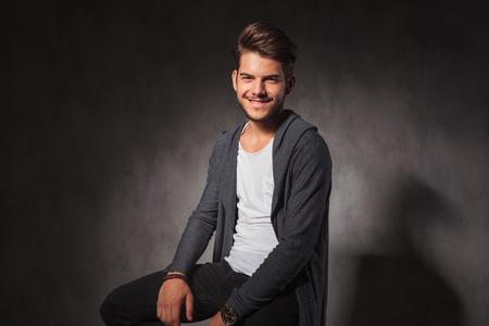 hombre flaco: Retrato de hombre joven feliz en el fondo del estudio sonriendo a la cámara mientras se está sentado