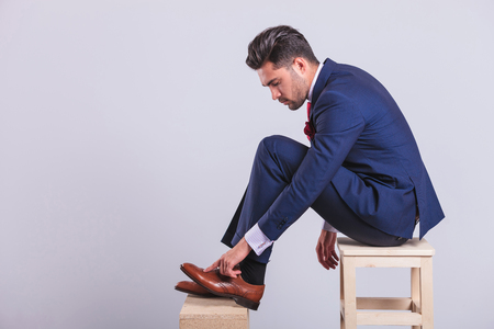 male fashion model: hansome man in suit sitting on chair in studio cleaning his brogue shoes