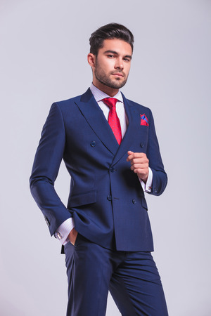上品なスーツのポケットに手でポーズ スタジオに立っての若い男 写真素材
