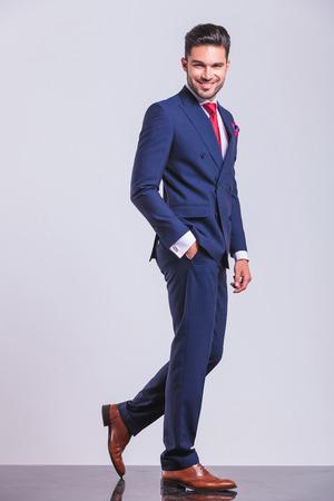 elegant man in suit walking away whith hand in pocket while posing Standard-Bild