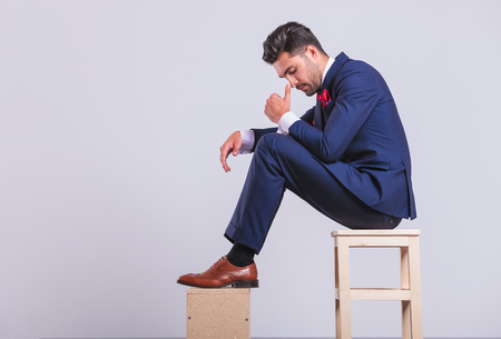 sit: attractive elegant man in suit sitting in studio looking down while touching his nose