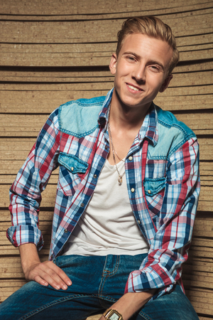 man shirt: portrait of smiling young man posing while sitting in studio with shirt open Stock Photo