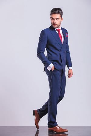 elegante: homme en costume d'affaires marche tout en détournant les yeux avec la main dans la poche