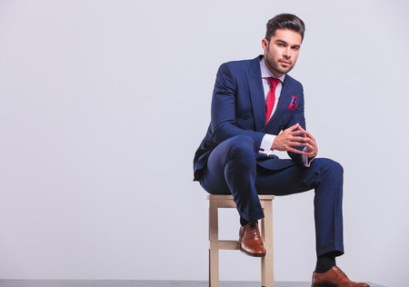 full suit: elegant man in business suit sitting in studio with palms touching while resting his leg on chair Stock Photo