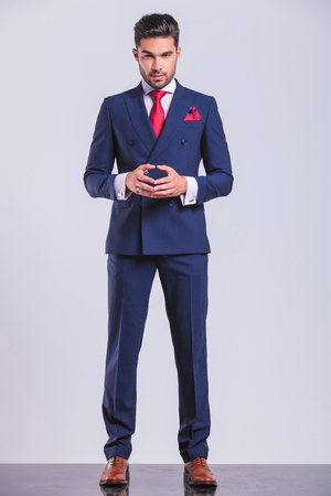 confident handsome business man posing while standing and touching his palms