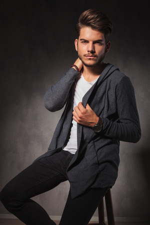 young male: portrait of man in studio sitting and touching his neck while looking at the camera Stock Photo