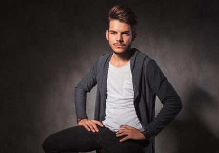 poses de modelos: retrato del hombre atractivo que presenta en fondo del estudio con las manos en la cintura mirando a la cámara